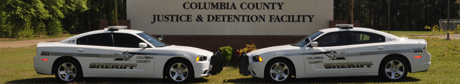 Two squad cars parked in front of the Columbia County Justice and Detention Facility